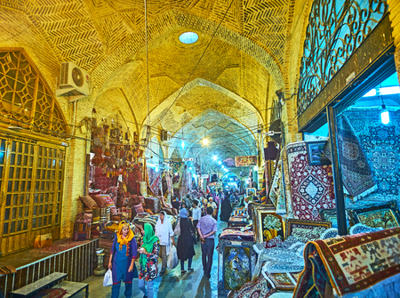 SHIRAZ, IRAN - OCTOBER 12, 2017: The long row of carpet stores in Vakil Bazaar is the best place to feel atmosphere of Eastern market, on October 12 in Shiraz.