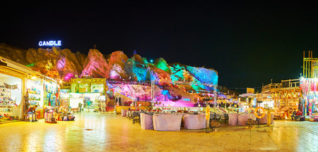 SHARM EL SHEIKH, EGYPT- DECEMBER 15, 2017: The restaurant court in Old Souk of resort, outdoor cafes are surrounded by tourist stalls, the rocks, illuminated in bright colors are seen on background, on December 15 in Sharm El Sheikh. Editorial