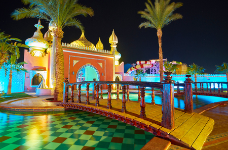 SHARM EL SHEIKH, EGYPT- DECEMBER 15, 2017:The evening walk in scenic garden of Fantasia Palace with ponds, fountains, Arabic style pavilions, alcoves and palms, on December 15 in Sharm El Sheikh. Banco de Imagens - 93582996