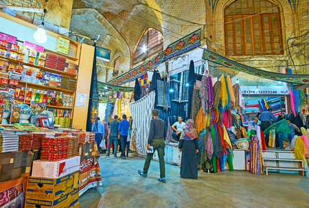 SHIRAZ, IRAN - OCTOBER 12, 2017: The stores in Foursquare hall in old Vakil Bazaar, local vendors offers fabrics, spices, sweets and other goods, on October 12 in Shiraz.