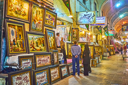 SHIRAZ, IRAN - OCTOBER 12, 2017: The row of stores in Vakil Bazaar, specializing on framed tapestries with different themes - inscriptions from Quran, still life, reproductions of famous pictures, portraits, on October 12 in Shiraz.