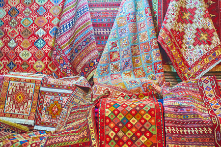 The complex geometric, floral, stellar and other patterns on colored woven carpets in stall of Vakil Bazaar, Shiraz, Iran. Editorial