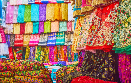 The wide range of bright colored fabrics, decorated with rhinestones, embroideries, lace, prints and lurex, Vakil Bazaar, Shiraz, Iran.