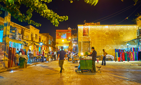 SHIRAZ, IRAN - OCTOBER 12, 2017: The evening street of Bazar-e No with open stores, street food vendor with a cart and illumnated buildings, on October 12 in Shiraz.