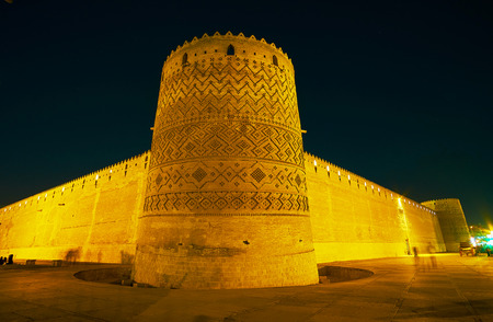The corner view of Arg Karim Khan with massive ramparts and leaning tower, covered with ornaments, Shiraz, Iran.