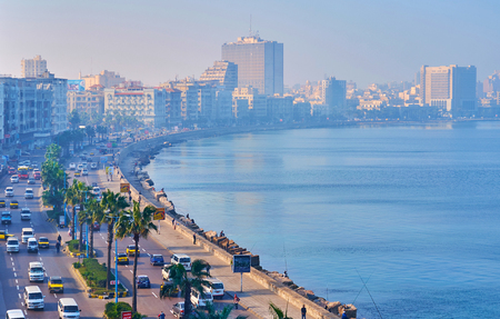 ALEXANDRIA, EGYPT - DECEMBER 17, 2017: The light morning haze over the seaside promenade - Corniche, with fast chaotic traffic and tall palm trees, on December 17 in Alexandria.