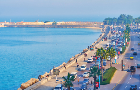ALEXANDRIA, EGYPT - DECEMBER 17, 2017: The foggy Corniche embankment in the early morning, transport ride along the road and people walk on the seaside promenade, on December 17 in Alexandria.