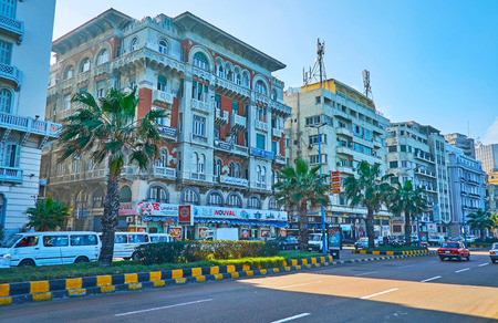 ALEXANDRIA, EGYPT - DECEMBER 17, 2017: The walk along the Corniche avenue with preserved historic mansions, beautiful palms and busy road, on December 17 in Alexandria.