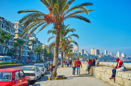 ALEXANDRIA, EGYPT - DECEMBER 17, 2017: The seaside walking area in Corniche avenue is the popular place among local students, spending their free time with friends there, on December 17 in Alexandria.