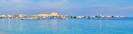 The blue waters of Mediterranean sea with colored fishing boats in Eastern harbor and medieval Qaitbay Citadel on background, Alexandria, Egypt.