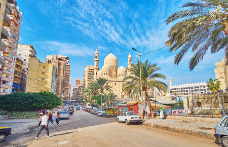 ALEXANDRIA, EGYPT - DECEMBER 17, 2017: The walk along the residential neighborhood with modern high-rises and  Sidi Yaqut al-Arshi mosque on the distance, on December 17 in Alexandria. Editorial