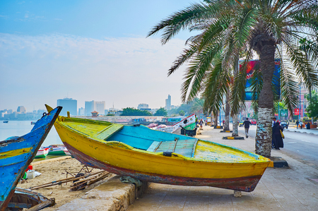 ALEXANDRIA, EGYPT - DECEMBER 17, 2017:  The fishing wooden boat occupies the pedestrian walkway in Corniche avenue and waits for repair, on December 17 in Alexandria. Editorial