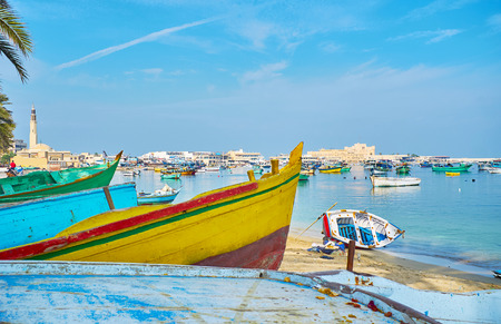 The view on Eastern harbor and Qaitbay citadel, through the bows of old wooden boats, Alexandria, Egypt.