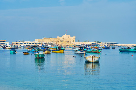 The view of Eastern harbor, full of small fishing boats, the medieval Qaitbay citadel is located on the distance, Alexandria, Egypt.