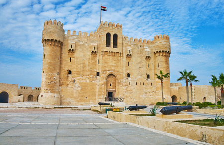 The facade of Qaitbay castle with towers from each side, battlements and loopholes, Alexandria, Egypt.