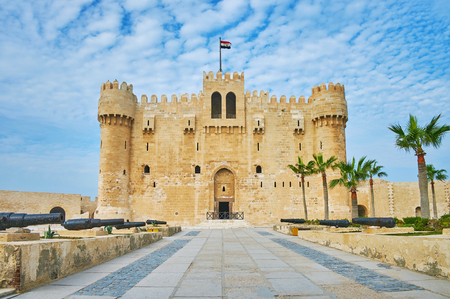 The alley with cannons leads to the entrance to Qaitbay Fort, one of the notable city landmarks, Alexandria, Egypt.