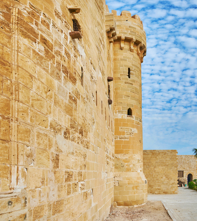 The huge defensive wall of Qaitbay citadel with a view on its tower , Alexandria, Egypt.