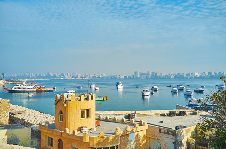 The ramparts of Qaitbay citadel overlooks the Eastern harbor with yachts and fishing trawlers, the foggy housing of Alexandria stretches along the coast on background, Egypt. Stock Photo