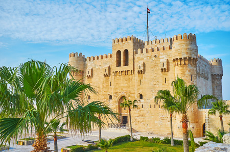 The old stone castle of Qaitbay is seen through the green palms, growing in its garden, Alexandria, Egypt.