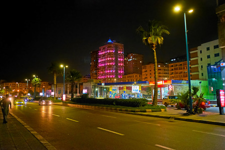 ALEXANDRIA, EGYPT - DECEMBER 17, 2017: The evening walk along El Gaish road with a view on brightly illuminated buildings, stores and cafes, on December 17 in Alexandria.