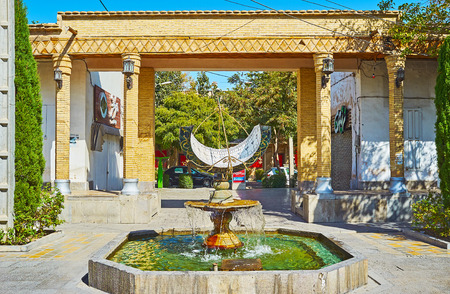 ISFAHAN, IRAN - OCTOBER 20,2017: The beautiful fountain with sundial in Julfa square of Armenian neighborhood, the decorative brick gates are seen on background, on October 20 in Isfahan.