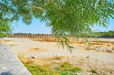 The view on the dried up Zayandeh river and medieval Si-o-se-pol bridge through the green branches of willow tree, Isfahan, Iran. Stock Photo