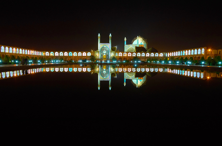 The bright evening lights make medieval Naqsh-e Jahan square one of the most romantic places in city and the clear surface of the pond reflects the buildings, Isfahan, Iran.