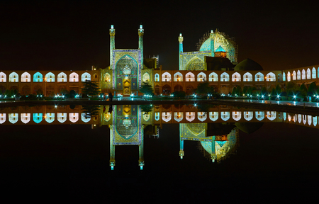 The clear night reflection of illuminated Royal Mosque and pavilions of Grand Bazaar in black waters of pond in the middle of Naqsh-e Jahan square of Isfahan, Iran. Stock Photo