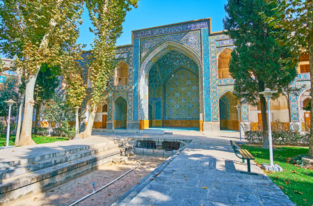 The portal, decorated with colored tiled patterns is seen through the greenery of garden of Chaharbagh madraseh, Isfahan, Iran. Editorial