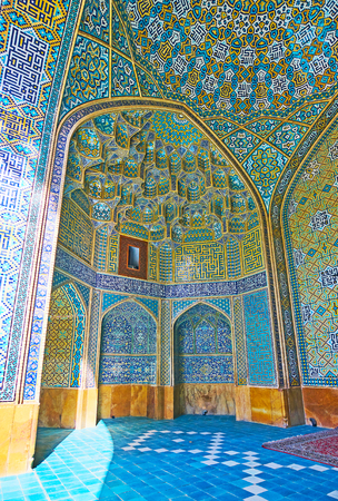 The complex niche in portal of Chaharbagh madraseh is decorated with muqarnas (honeycomb) elements, calligraphy and fine Islamic patterns of glazed tiles, Isfahan, Iran. Editorial