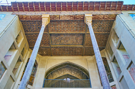 ISFAHAN, IRAN - OCTOBER 20, 2017: The  carved wooden ceiling and slender pillars of the porch of Hasht Behesht Palace, famous for its outstanding decorations, on October 20 in Isfahan.
