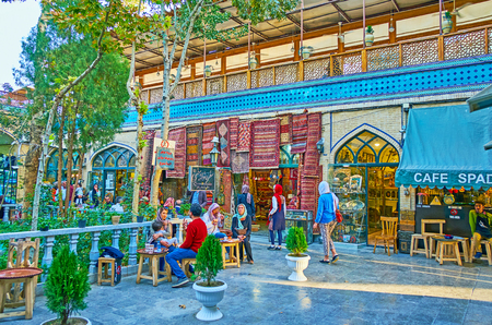 ISFAHAN, IRAN - OCTOBER 20, 2017: The tourists and locals enjoy the tiny garden in hidden yard of Grand Bazaar, small cafe and teahouse offer refreshing drinks in shade of tall trees, on October 20 in Isfahan.