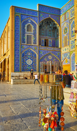 ISFAHAN, IRAN - OCTOBER 20, 2017: The  bright blue tiled portal (iwan) of Sheikh Lotfollah Mosque behind the souvenirs of tourist stall in Naqsh-e Jahan square, on October 20 in Isfahan.