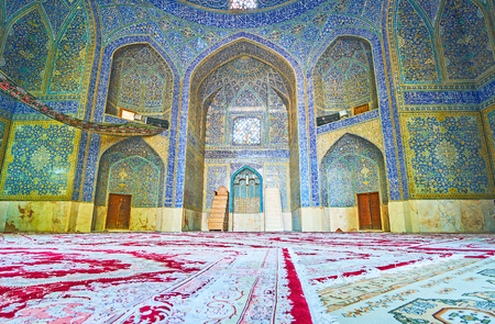 ISFAHAN, IRAN - OCTOBER 20, 2017: The prayer hall of the old mosque in Chaharbagh madraseh, the walls are decorated with fine patterns and Arabic calligraphy of glazed tile, on October 20 in Isfahan.