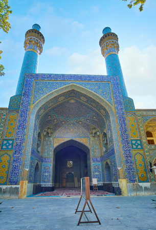 The giant entrance portal of the medieval mosque of Chaharbagh madraseh with two slender minarets also decorated with bright blue tiled patterns, Isfahan, Iran.