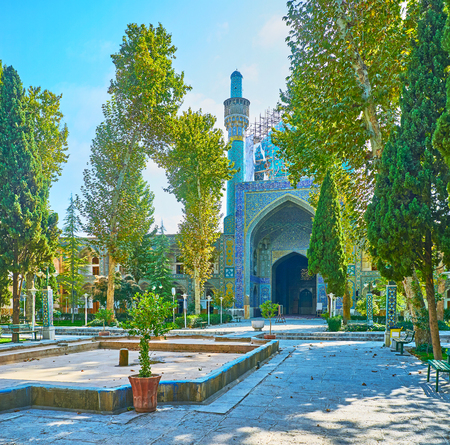 The pleasant garden with tall lush trees opens the picturesque views on the medieval portals, living buildings and the mosque of Chahrbagh madraseh, Isfahan, Iran. Stock Photo