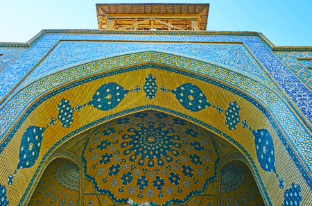 The yellow cupola of Chaharbagh madraseh is decorated with bright blue ornamental details, Isfahan, Iran.