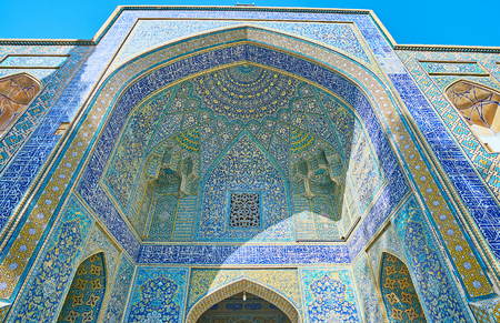 The portal (iwan) of Chaharbagh madraseh with complex tiled patterns in blue gamma, scenic Arabic calligraphy, numerous niches and muqarnas details, Isfahan, Iran. Stock Photo