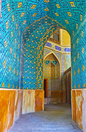 ISFAHAN, IRAN - OCTOBER 20, 2017: The bright blue corridor of Chaharbagh madraseh leads to the summer mosque prayer hall, richly decorated with mosaics and tiled patterns, on October 20 in Isfahan.