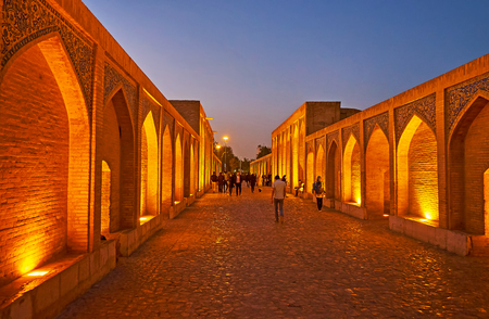 ISFAHAN, IRAN - OCTOBER 20, 2017: The evening walk along the  Khaju bridge with the view on brick niches on both sides, on October 20 in Isfahan. Editorial