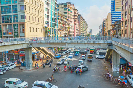 YANGON, MYANMAR - FEBRUARY 14, 2018: The pedestrian bridge on intersection of Anorata road and Lanmadaw street - always busy and noisy areas of Chinatown, on February 14 in Yangon.