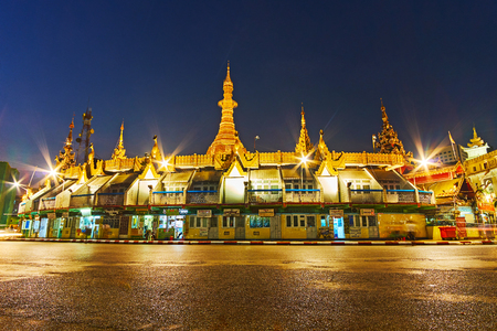 YANGON, MYANMAR - FEBRUARY 14, 2018: The bright evening illumination of Sule Pagoda, its golden stupas shine in dark sky, on February 14 in Yangon. Redactioneel