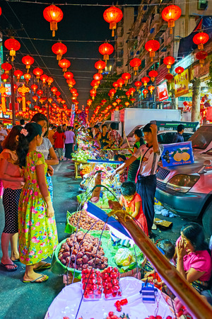 YANGON, MYANMAR - FEBRUARY 14, 2018: Locals and tourists enjoy the  the Spring Festival (Chinese New Year) celebration, visiting holiday market on Maha Bandula Road, on February 14 in Yangon. Editorial