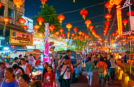YANGON, MYANMAR - FEBRUARY 14, 2018: Walk in crowded Maha Bandula Road of Chinatown during Chinese New Year celebration, avenue is decorated with numerous red lanterns, on February 14 in Yangon.