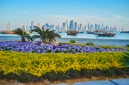 Corniche promenade is perfectly decorated with beautiful flower beds, tiny palms and trimmed bushes, Doha, Qatar.