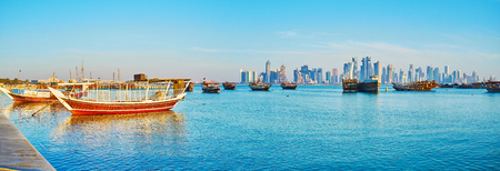 The seaside promenade of Doha is popular tourist place, its famous for picturesque views of traditional dhow boats in harbor and modern skyscrapers on background, Qatar. Stock Photo