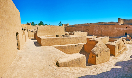 The walk among adobe ruins and tall ramparts of old Arg-e Rayen, well preserved in desert of Kerman Province, Iran. Editorial