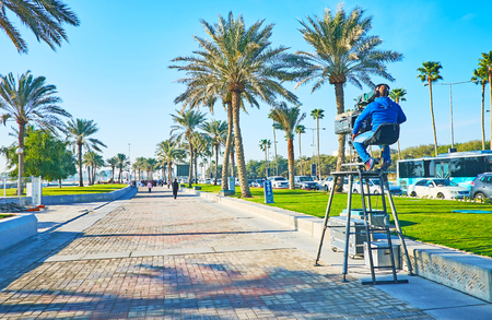 DOHA, QATAR - FEBRUARY 13, 2018: Cameraman conducts live TV broadcast from Corniche promenade in business Al Dafna district during the Day of Sport, on February 13 in Doha. Editorial