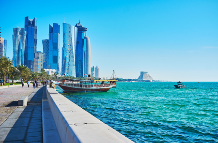 The pleasure boats at the coast of West Bay, the glass skyscrapers of Al Dafna business district are seen on background, Doha, Qatar.