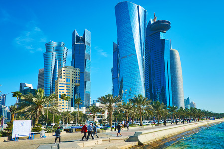 DOHA, QATAR - FEBRUARY 13, 2018: Al The quarters of Al Dafna district with shining glass skyscrapers and row of lush green palms along the Corniche promenade, on February 13 in Doha.